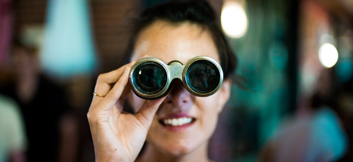 Woman looking through binoculars. Source: Chase Clark Unsplash.com